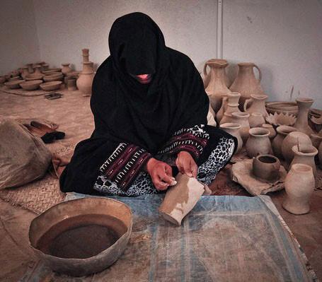 une femme noire lors de la création de poterie